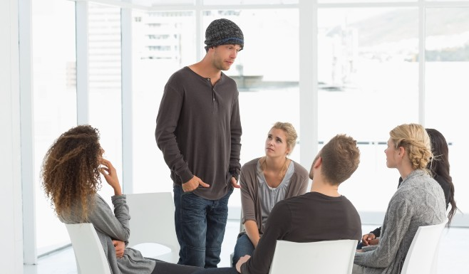 young man in group therapy at a drug rehab facility.